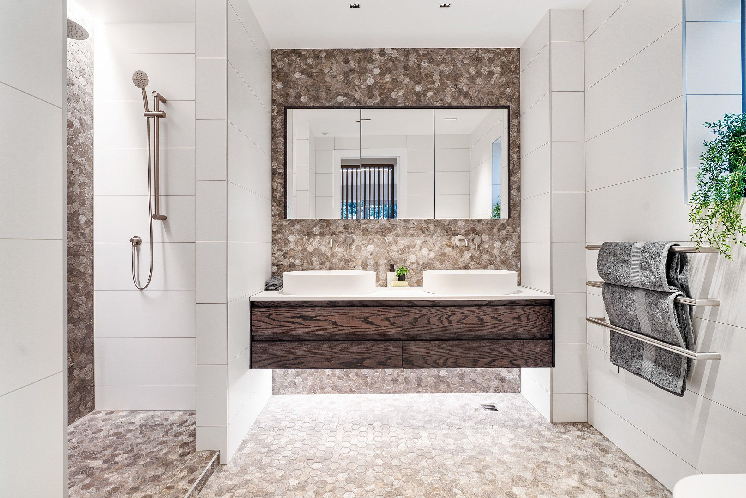Modern bathroom with shower and vanities